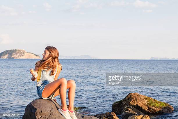teenage girl enjoys icecream at seaside - alleen één tienermeisje stockfoto's en -beelden