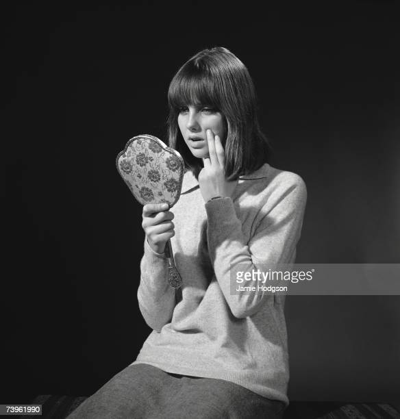 A teenage girl examines her skin for spots March 1965
