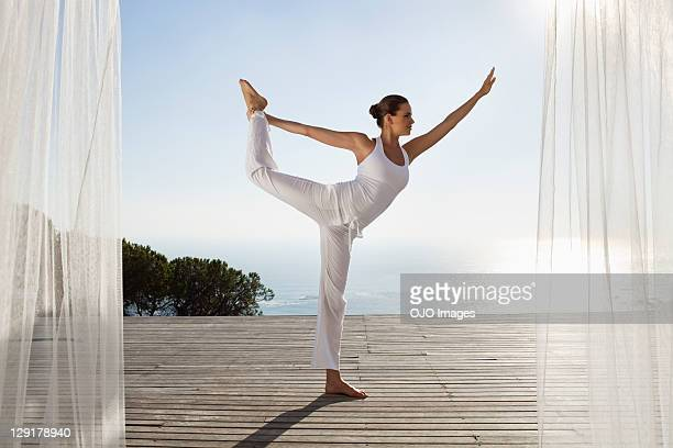 Teenage girl exercising against clear sky