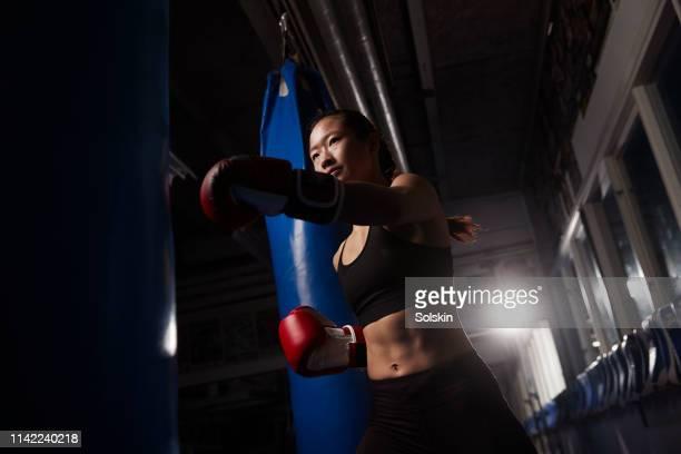 Teenage girl exercising using boxing bags