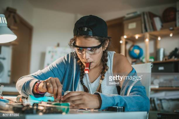 Teenage girl experimenting with electronics