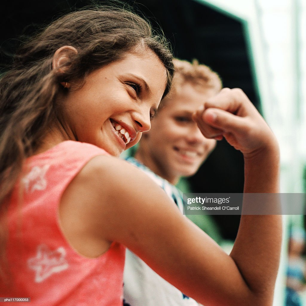 Teenage girl flexing arm muscles, smiling : Stockfoto