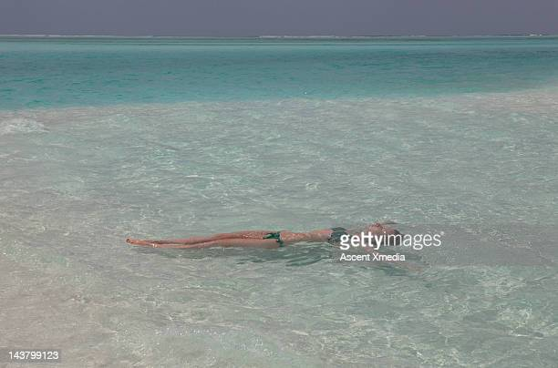 teenage girl floating in the shallows of a lagoon - number of people stock photos and pictures