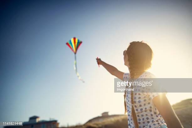teenage girl flying a kite on a beach - unusual angle stock pictures, royalty-free photos & images
