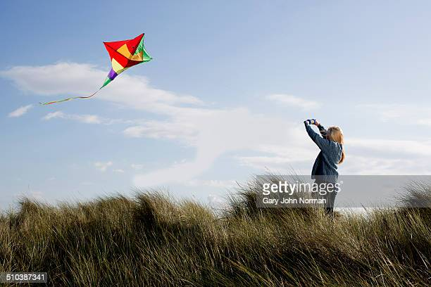 Teenage girl flying a kite on the beach.