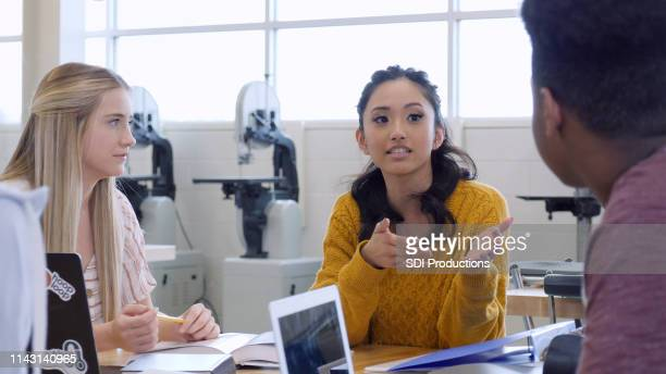 teenage girl gestures as she speaks to classmate - debate stock pictures, royalty-free photos & images