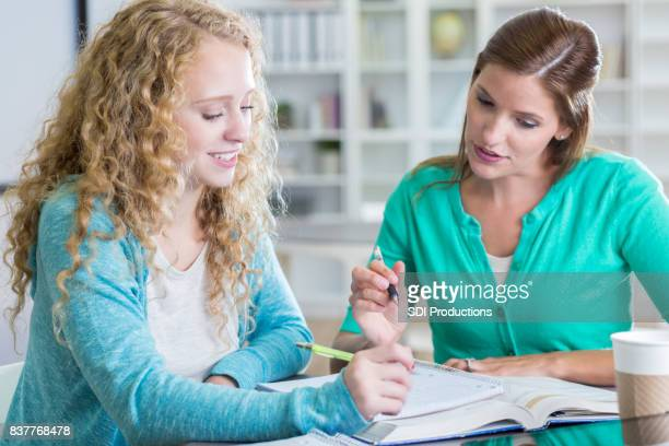 teenage girl gets help from homework tutor at school - one teenage girl only stock pictures, royalty-free photos & images