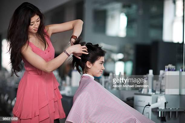 Teenage girl getting hair done in salon