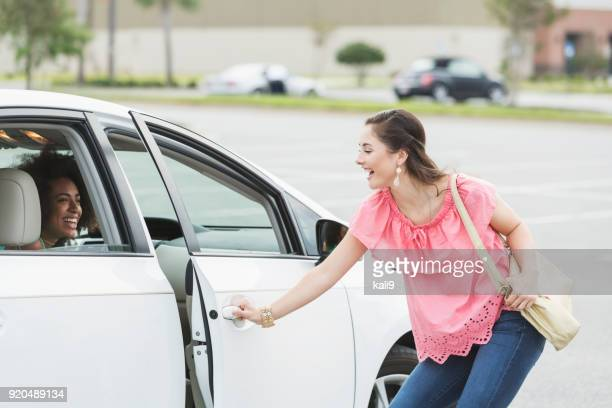 Teenage girl getting into friend's car