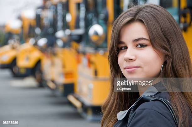 teenage girl getting  on a yellow school bus. - ogphoto stock photos and pictures