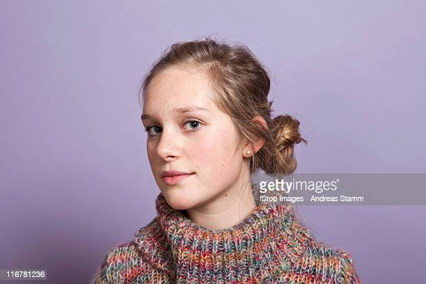 a teenage girl give a sideways glance to the camera, portrait, studio shot - purple background stock photos and pictures