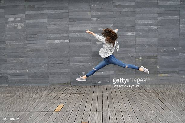 Teenage Girl Going Grand-Jete Against Wall