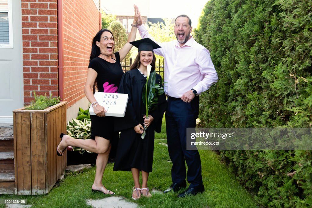 Teenage girl graduation from primary school family portrait in backyard. : Stock Photo