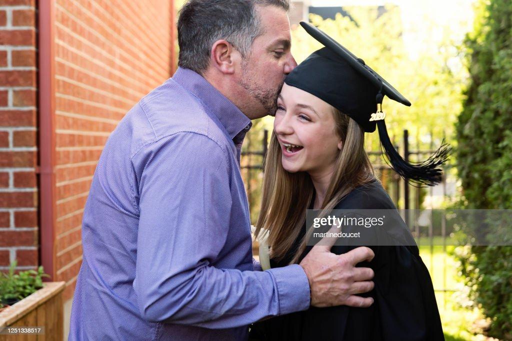 Teenage girl graduation from primary school family portrait in backyard. : Stock Photo