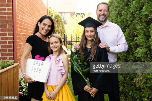 """teenage girl graduation from primary school family portrait in backyard. - """"martine doucet"""" or martinedoucet stock pictures, royalty-free photos & images"""