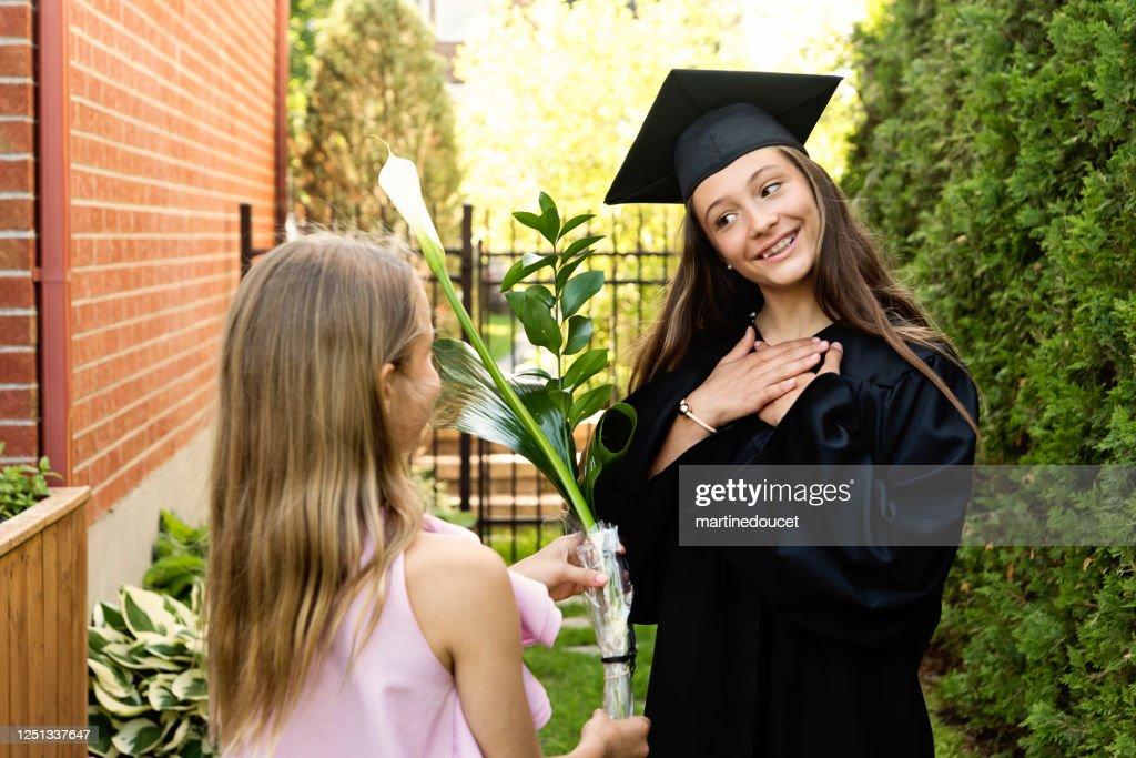 Teenage girl graduation from primary school portrait in backyard. : Stock Photo