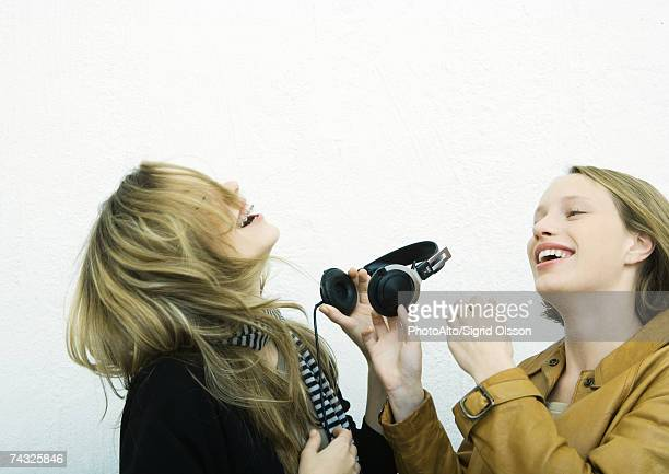 Teenage girl handing friend headphones
