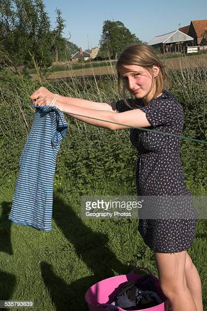 teenage girl hanging up clothes on a washing line in Suffolk England