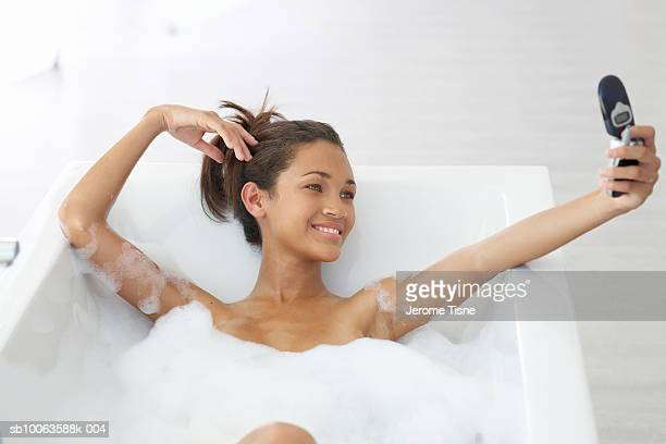 Teenage girl (16-17) having bubble bath, holding mobile phone, smiling