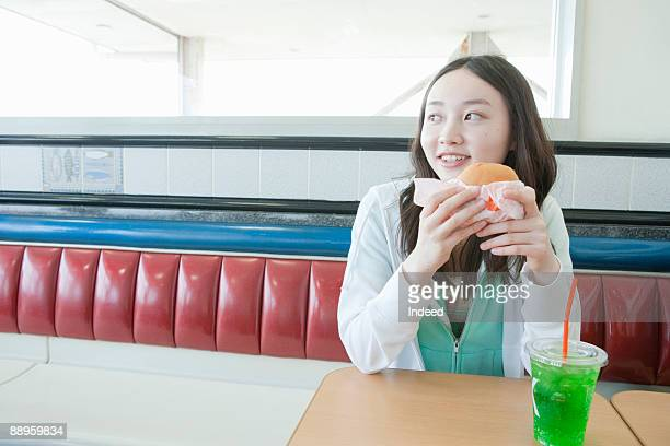 teenage girl having burger and soda - teenagers only stock pictures, royalty-free photos & images