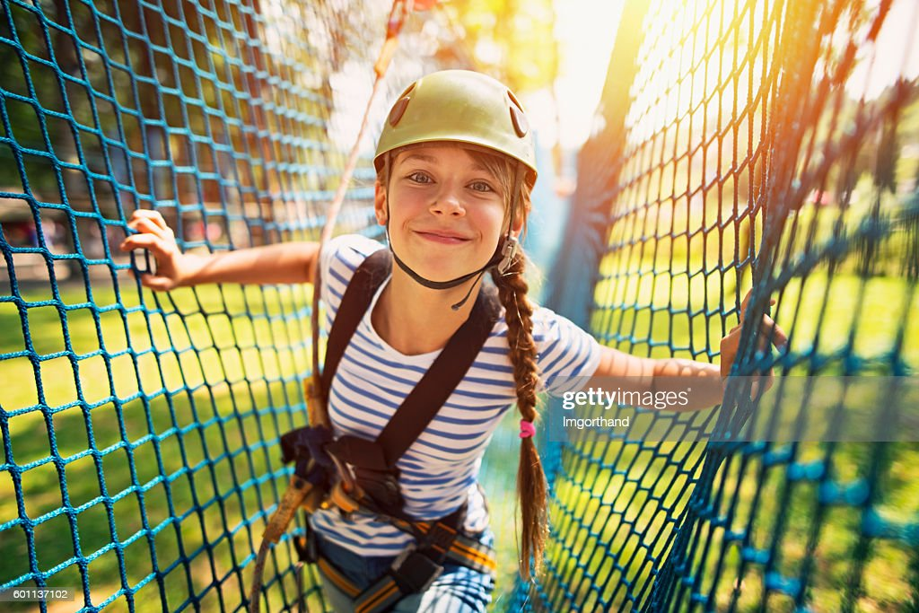 Teenage girl having fun in ropes course adventure park : Stock Photo