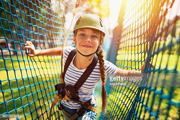 teenage girl having fun in ropes course adventure park - sports equipment stock pictures, royalty-free photos & images