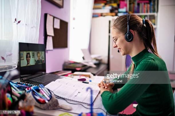tiener die online les in haar ruimte heeft. - afgelegen stockfoto's en -beelden