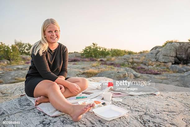 Teenage girl having picnic on rock