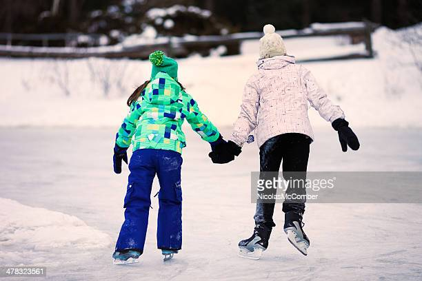 Teenage girl helping her sister skate