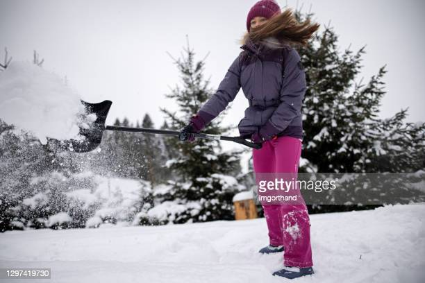 teenage girl helping to remove snow from the backyard - snow shovel stock pictures, royalty-free photos & images