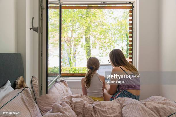 teenage girl helping younger sister with remote school work - bedroom stock pictures, royalty-free photos & images