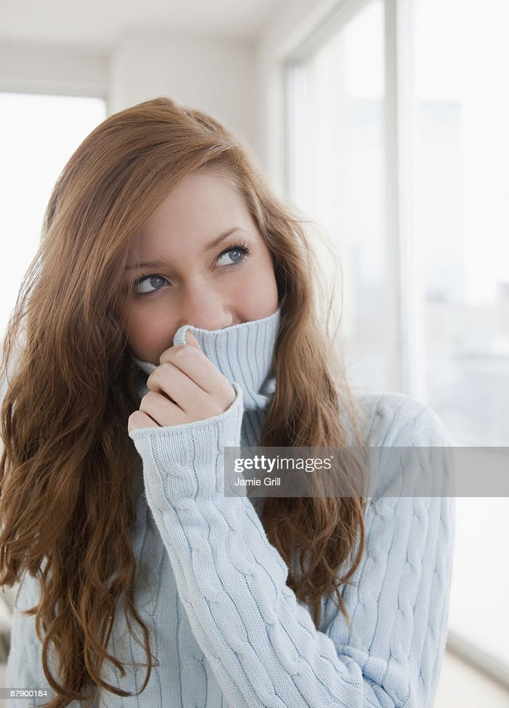 Teenage girl hiding her face with sweater : Stock Photo