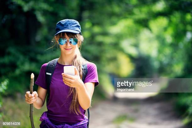 Teenage girl hiker checking route on smartphone.