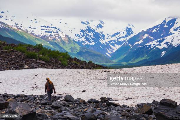 a teenage girl hikes off-trail near byron glacier in portage valley on a rainy day in early summer - miley fotografías e imágenes de stock