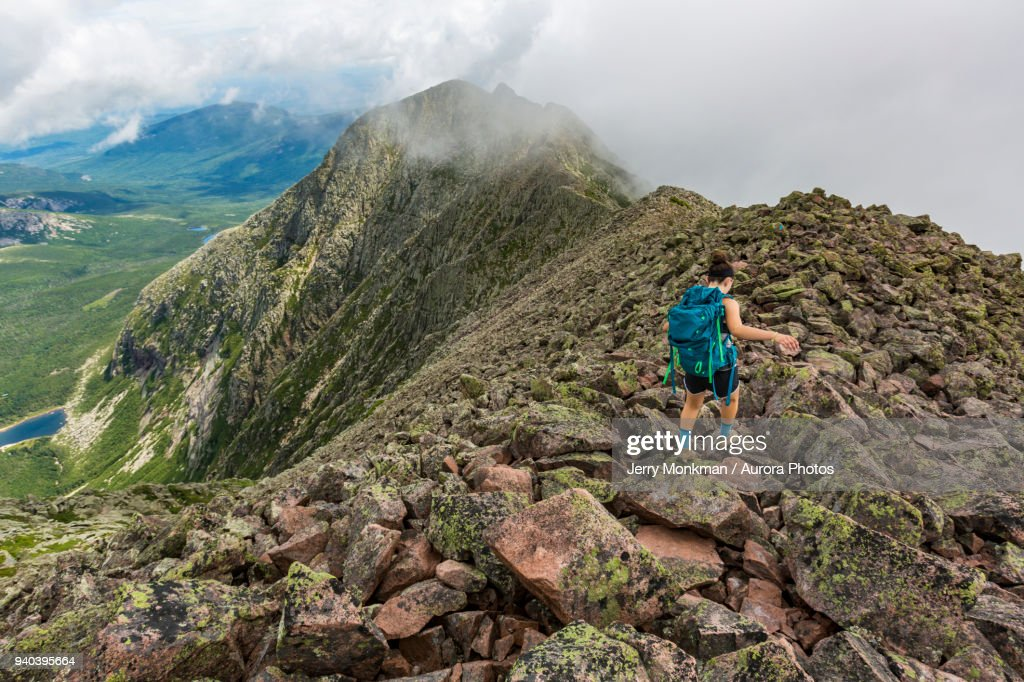 Teenage girl hiking along mountain ridge at Knife Edge Trail on Mount Katahdin in Baxter State Park, Maine, USA : Stock Photo