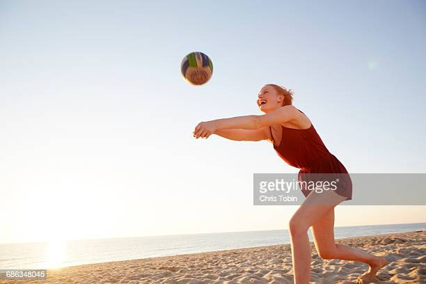 Teenage girl hitting volleyball at the beach