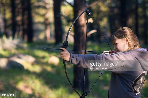 Teenage girl holding a bow and arrow.