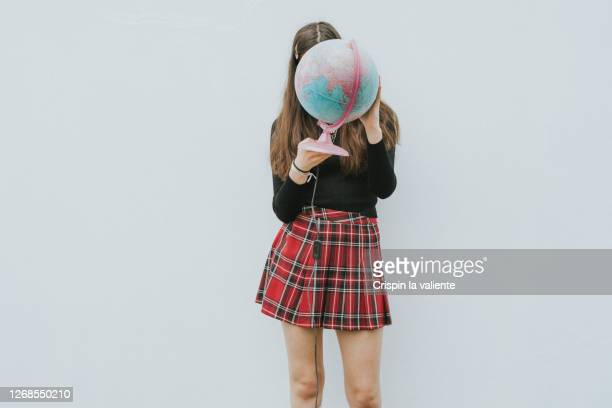 teenage girl holding a earth ball - skirt stock pictures, royalty-free photos & images