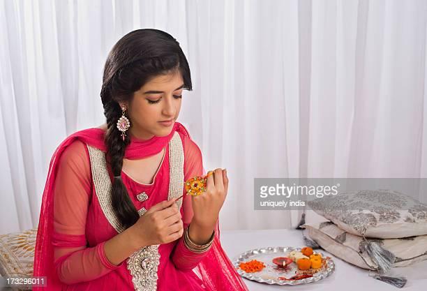 teenage girl holding a rakhi at raksha bandhan - raksha bandhan stock photos and pictures