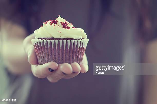 Teenage girl holding a red velvet cupcake