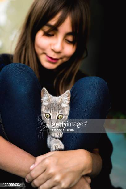 Teenage Girl Holding An Adorable Kitten With Amber Eyes
