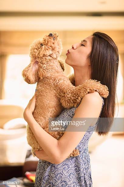 Teenage girl holding and playing with dog