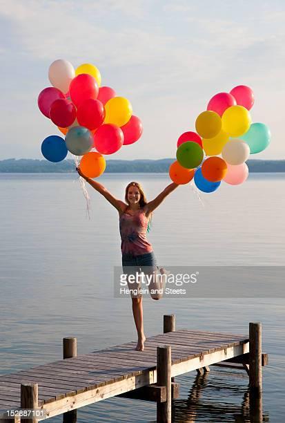 Teenage girl holding balloons on pier