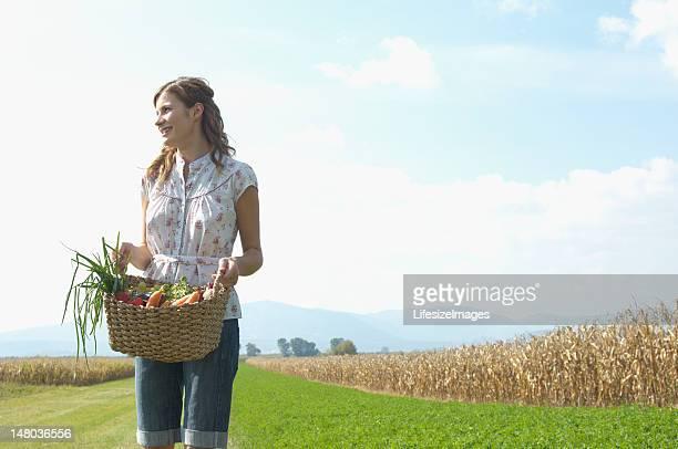 Teenage girl (16-18) holding basket of vegetables, looking to si