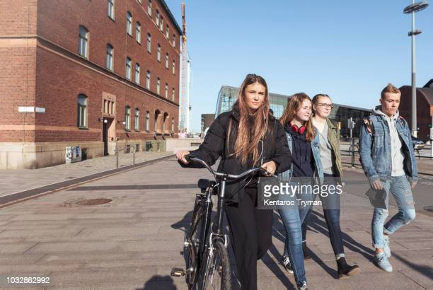 teenage girl holding bicycle while walking with friends on footpath in city against clear sky - seulement des adolescents ou adolescentes photos et images de collection
