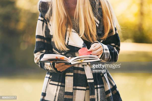 Teenage girl holding book and autumn leaves