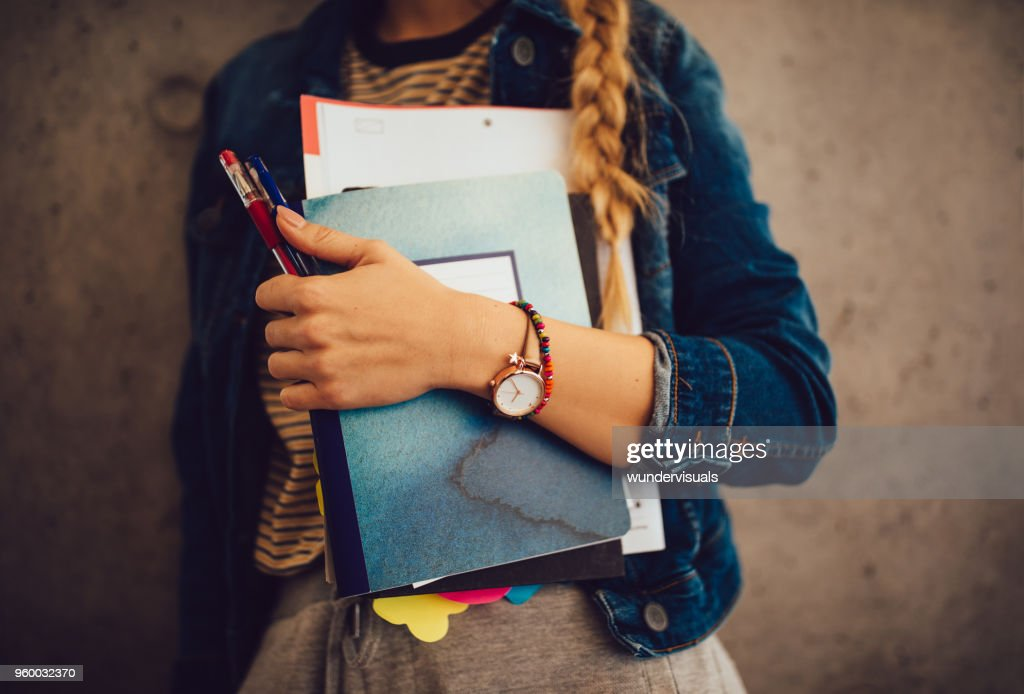 Teenage girl holding books, notebooks and pencils standing against wall : Stock Photo