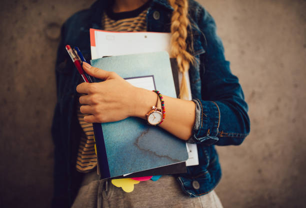 teenage girl holding books, notebooks and pencils standing against wall - preparation stock pictures, royalty-free photos & images