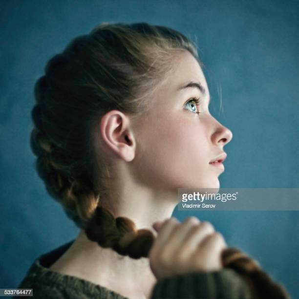 Teenage girl holding braid