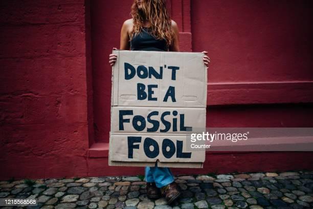 teenage girl holding climate school strike protest sign - demonstrant stock-fotos und bilder